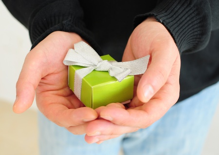 gifting: Close up of male hands giving small gift