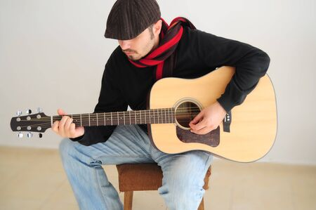 Young caucasian man playing the guitar photo