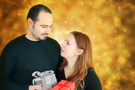 gifting: Young couple exchanging  gifts for holidays Stock Photo