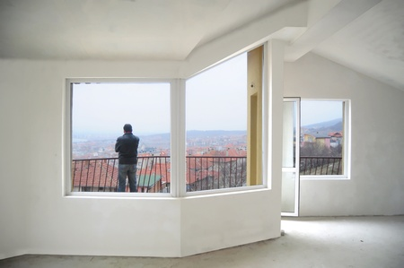 balcony window: young man on the balcony of a new unfinished building Stock Photo