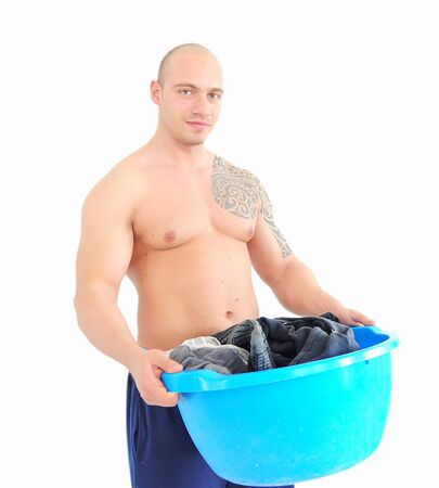 young muscular man with laundry basket photo