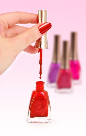 Woman holding brush over opened bottle of red nail polish, bottles on the background