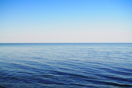 Calm sea extending to the horizon and clowdless sky Stock Photo