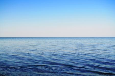 Calm sea extending to the horizon and clowdless sky Standard-Bild