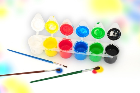 Set of tempera paints and brusheson colorful background photo