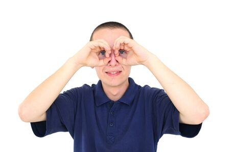 Young man looking through his fingers like binoculars Stock Photo