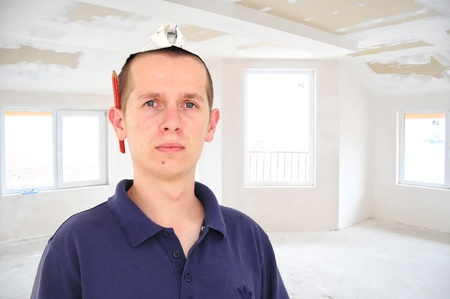 Young serious man with  paper hat in newly build unfinished room Stock Photo - 12355602