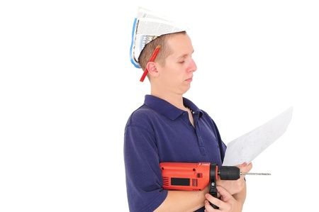 Young serious man with drill and paper hat reading blueprints