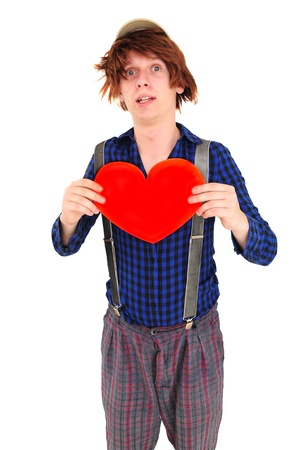 Goofy young man with funny hair and clothes holding heart photo