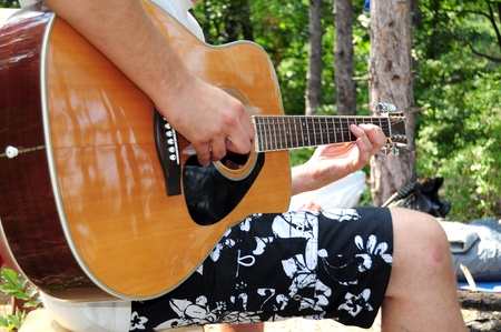 Young caucasian man playing the guitar outdoors photo