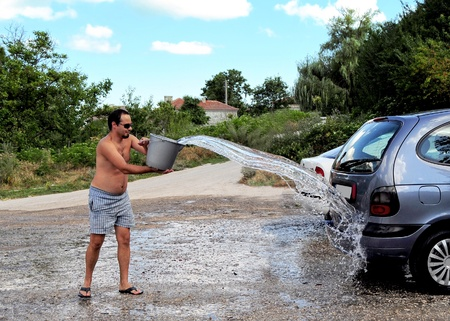Young man throwing water from bucket, washing the car Standard-Bild