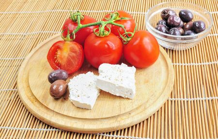 Fresh tomatoes, olives and white cheese on wooden board, cup of olives beside photo