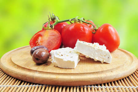 Closeup of fresh tomatoes, olives and white cheese on wooden board