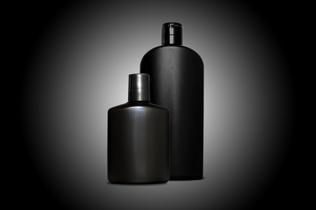 Set of two bottles of cosmetic products for men in black on black background photo