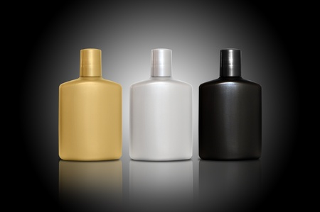 Set of three bottles of cosmetic products for men - silver, gold, black on black background photo