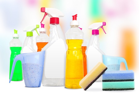 Many colorful bottles of cleaning products and spounges  photo