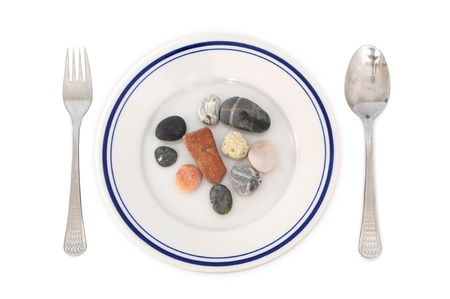 Concept of digestion problems or poverty - stones in a plate