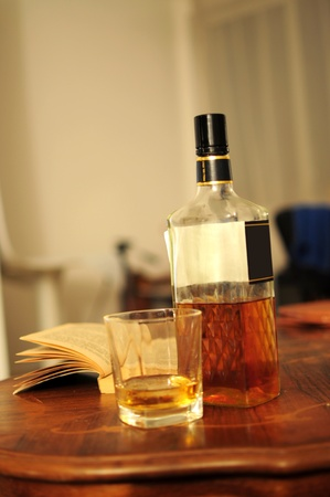 Glass of whiskey, bottle and opened book on home table photo