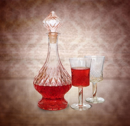 Vintage wine decanter and two glasses on retro background photo