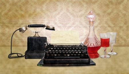 Vintage telephone, typewriter and wine bottle