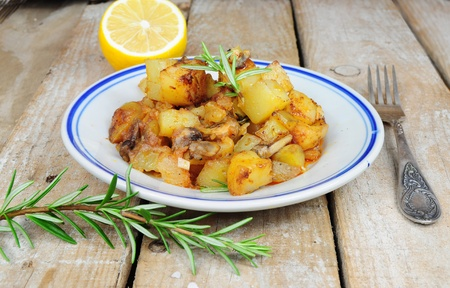 Roasted potatoes and rosemary country style on wooden background photo