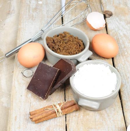 Ingredients for cake - flour, brown sugar, eggs, cinnamon, chocolate