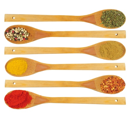 Various colorful dried spices in wooden spoons - parsley, pepper, cardamon, curry, chilli, paprika photo