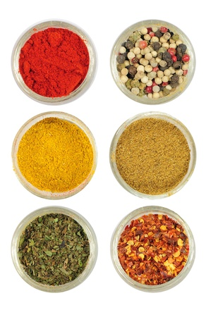 Various colorful spices in round bowls - paprika, pepper, curry, cardamon, oregano, chilli photo