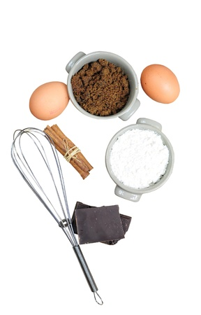 Ingredients for cake - flour, brown sugar, eggs, chocolate, cinnamon, isolated on white