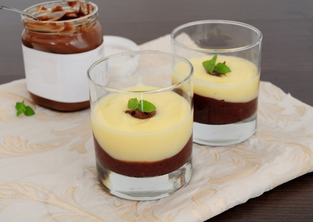 Chocolate and vanilla cream, served in glasses, jar of choco spread in the background photo