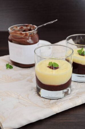 Chocolate and vanilla cream, served in glasses, jar of chocolate spread in the background photo
