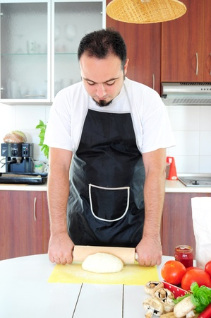 Young man in apron in kitchen, rolling out dough Stock Photo - 14785375