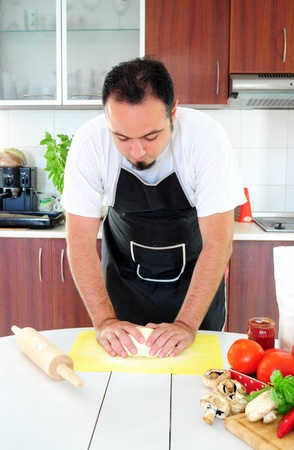 Young man in apron in kitchen, kneading dough Stock Photo - 14785370
