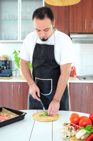 Young man in apron in kitchen cutting herbs Stock Photo