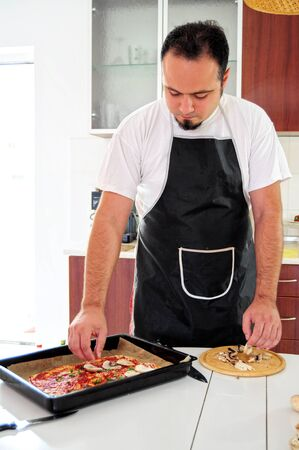 Young man in apron in kitchen preparing pizza Stock Photo - 14785378