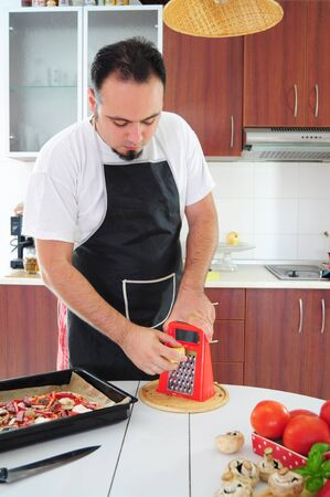 parmezan: Young man in apron in kitchen grating cheese