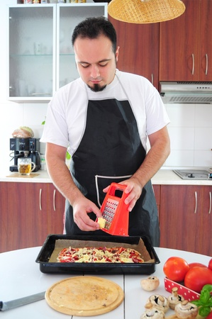 Young man in apron in kitchen grating cheese over pizza