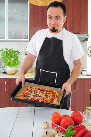 Young man in apron in kitchen with ready homemade pizza Stock Photo - 14785377