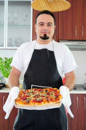 Young man in apron in kitchen with ready homemade pizza photo