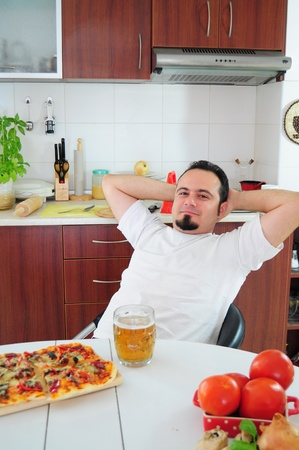 Young man in kitchen enjoying homemade pizza and beer photo