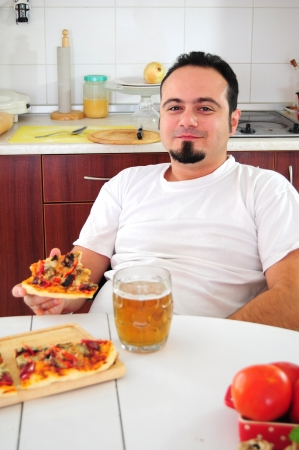 Young man in kitchen eating homemade pizza drinking beer photo