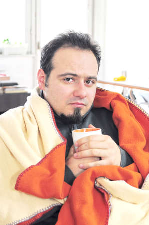 Young man in blanket holding cup of tea