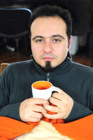 Young man in blanket holding cup of tea Stock Photo - 16660961