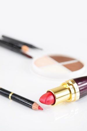 Closeup of red lipstick and pencil, eye-shadows and brushes in the background
