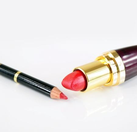 Closeup of red lipstick and pencil on white background
