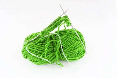 Green and yarn and needles and piece of knitting Stock Photo