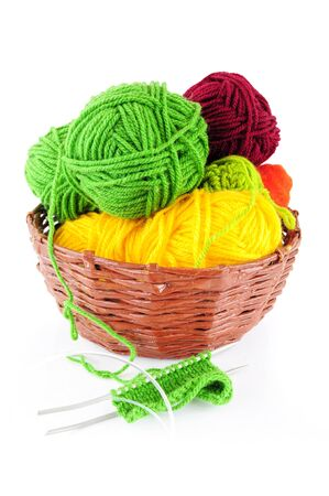 Colorful yarn and needles for knitting in wicker basket Stock Photo