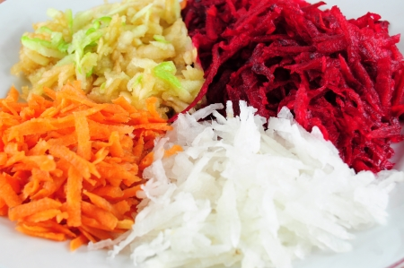 Salad from shredded beetroot, turnip, carrots and apple - closeup view Stock Photo