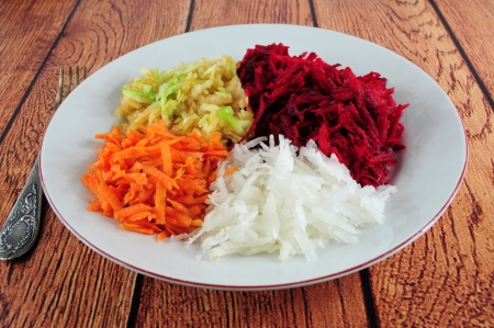 Salad from shredded beetroot, turnip, cattor and apple in a plate Stock Photo