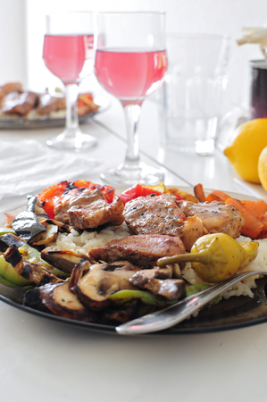 Dish with meat and vegetables served with rose wine Stock Photo